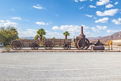 old steam tractor and wagons from 1894 serving the mine road in the death valley for Borate mining