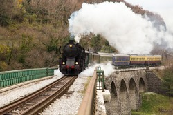 Old Steam Train on old Stone Bridge over big River