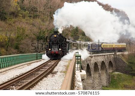 Old Steam Train on old Stone Bridge over big River