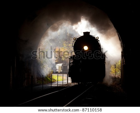 Old steam train pulling into a tunnel belching steam and smoke