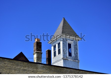 Old steep pointed rooftop lookout and masonry chimney with bright day clear blue sky as background.