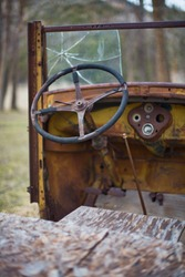 Old steering wheel and broken windshield of a rusting truck on a farm