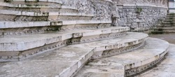 Old steps of white stone covered with mold running along a stone wall with bas-relief.
