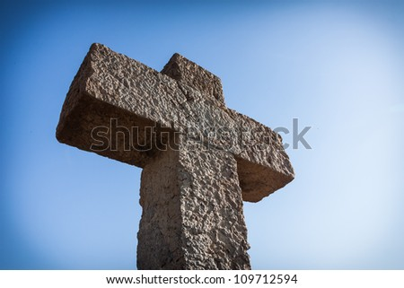 Old ston cross over blue sky - stock photo