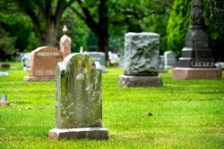 Old stone blank cemetery gravestone marker, headstones in background no name on tombstones , death, buried, die, life insurance, coronavirus, pandemic