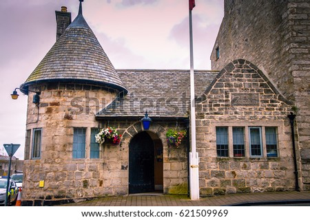 Old stone building facade with logo of the Isle of Man police station. Facade of the building. Stone building facade. Building facade in Old City Isle of Man. Stone wall. Elegant house architecture #621509969
