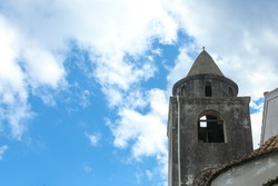 Old stone church bell tower with blue sky and white clouds