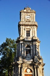 Old stone clock tower. Tower against a blue cloudless sky.