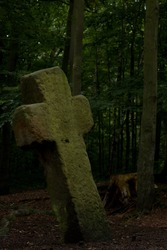 old stone conciliation cross in the forest