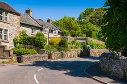 Old stone cottages and trees along the road. Countryside landscape of small village Ashford-in-the-Water in Derbyshire Peak District, England.