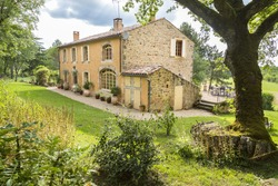Old stone country house in the South of France, surrounded by beautiful gardens. Glimpses of sun appear through clouds.