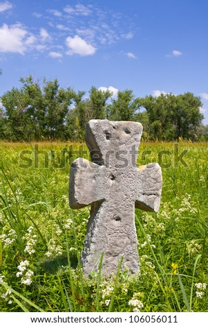 old stone cross on nice meadow