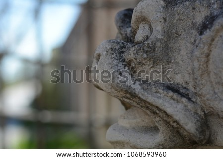 old stone gargoyle head statue in the castle garden in the historical town Mikulov, South Moravia, Czech republic #1068593960