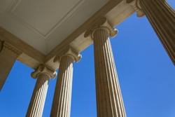Old stone greek style columns facade architecture building with blue sky