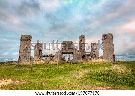 Old stone ruins of a castle, house or manor in medievel France with a dramatic grey and cloudy sky in the background and bright green grass in the foreground./ Old Stone Castle Ruins.
