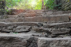 Old stone staircase, natural stone. A ray of the sun breaks through the foliage of trees. Selective focus, close up, copy space.