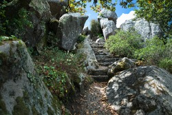 Old stone stairs carved in granite rock outcrop and cobblestone hiking path on slope of Sintra Mountains. Pena Park, Sintra - Cascais Natural Park, Lisbon Region, Portugal, Southwestern Europe.
