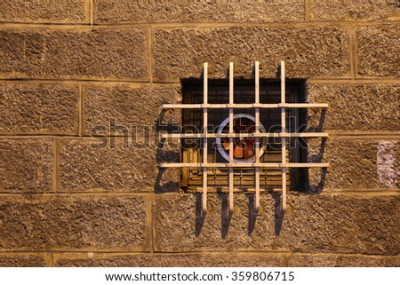 Old stone wall and barred ventilation window during the night time #359806715