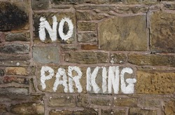 Old stone wall with White No Parking Hand Painted Sign in England