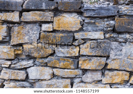 Old stone wall with yellow lichen texture