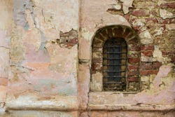 Old stone window old Russian style. Vintage window of a 16th-century Church with peeling bricks in Russia. Bars on an ancient window.