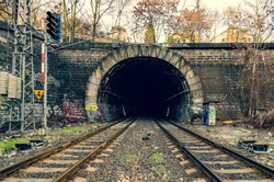 Old stony tunnel with double-track railway and traffic lights