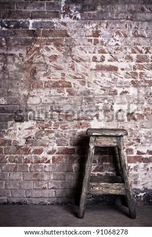 Old stool against an old brick wall