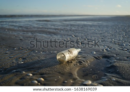 Old stranded glass bottle at baltic sea beach