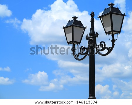 Old street decorated lamppost against cloudy blue sky background