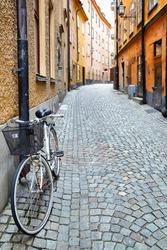 Old street in Stockholm, Sweden. Shallow DOF, focus on the bike