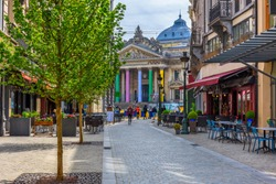 Old street with tables of cafe in center of Brussels, Belgium. Cozy cityscape of Brussels (Bruxelles). Architecture and landmarks of Brussels.