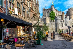 Old street with tables of cafe in Ghent (Gent), Belgium. Architecture and landmark of Ghent. Cozy cityscape of Ghent.