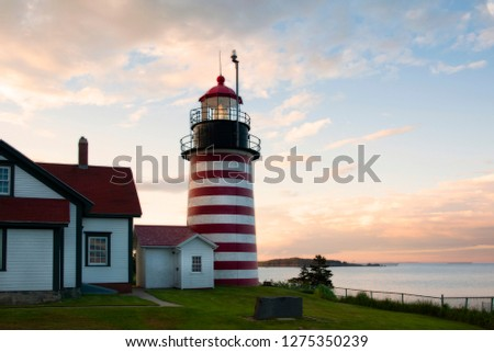 Old striped lighthouse tower of West Quoddy Head light shines brightly during sunset in northern New England. It uses an authentic Fresnel lens and is located in the easternmost point in the USA. #1275350239