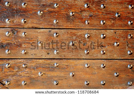 Old studded wooden door detail with multiple decorative studs