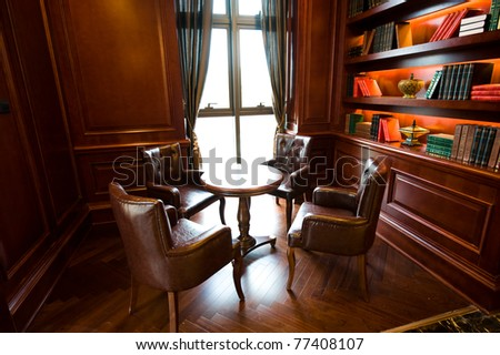 Old studying room with four leather armchairs and wooden table.