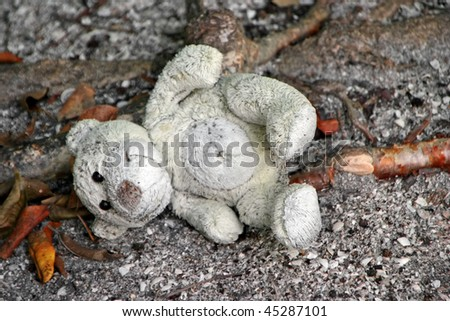 old stuffed teddy bear laying on ground
