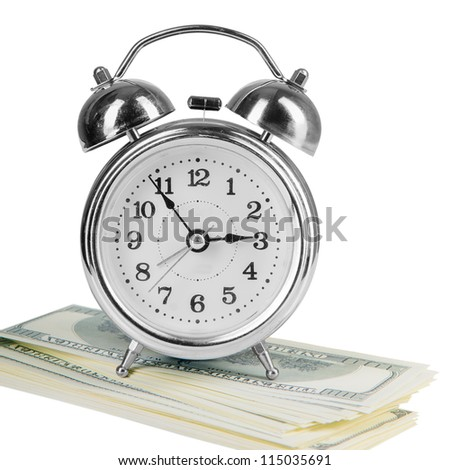 old style alarm clock and a lot of dollars.  isolated on white