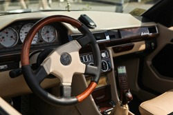 Old style classic luxury car interior. Steering wheel in focus, close up view. Natural skin and expensive elements coating. Old mobile phone, gear shift knob, glove box blurred in the background.