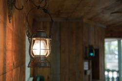 Old style copper lantern hanging in a traditional rustic wooden cabin in upstate New York.