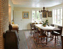 Old style dining room interior. Dining area With Bright walls With the around 100 years old table set. Brown wooden table set and old cabinet, wooden table near, Norwegain traditional wooden interior