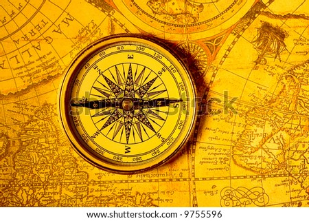 Old style gold compass on antique world map
