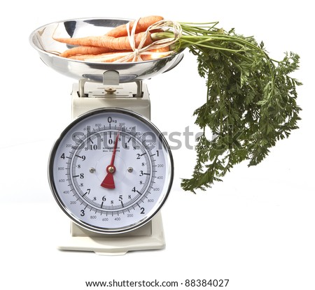 Old style kitchen scales with carrots on white background Isolated