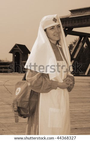 Old style picture with woman in nurse costume. Costume is authentic to the ones weared in time of  World War I.