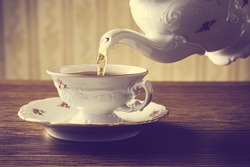 Old-style porcelain kettle pouring tea from jug to cup of tea on wallpaper background