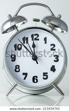 old style silver alarm clock with hammer and bells on top with hands at 7 minutes to midnight