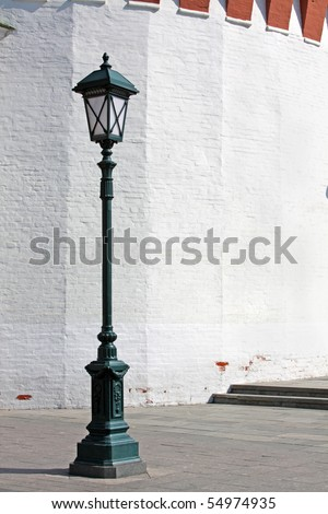 Old style street lamp in front of the wall of white brick