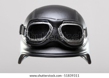 old-style us army motorcycle helmet with goggles, floating on gray background