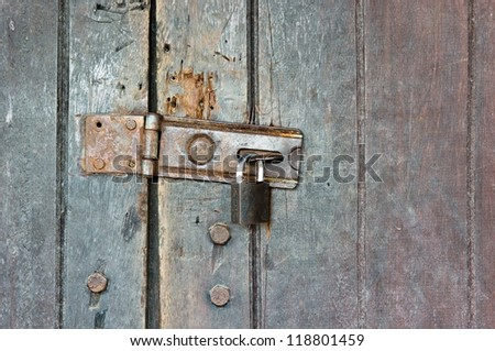 Old style wooden door locked with hasp and key