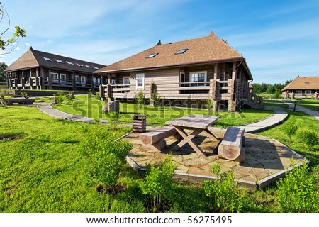 Old Style Wooden Log Cabins With Blye Sky And White Clouds