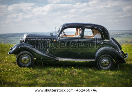 Photo of Old stylish Mercedes stands alone in the green field